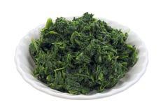 Het kleine dienen van gehakte spinazie in kom Royalty-vrije Stock Foto's