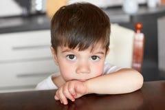 Het kleine donkere eyed mannelijke kind gluurt over rand van lijst, wacht op diner, stelt tegen vage keukenachtergrond Aantrekkel stock afbeeldingen