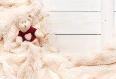 Het kleine gebreide babystuk speelgoed draagt is behandeld met een warme deken stock foto's