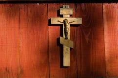 Het kleine houten kruisbeeld hangen op muur Stock Afbeelding