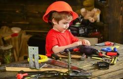Het kleine jong geitje spelen met boor en schroefbouten Zijaanzichtjongen in oranje helmzitting bij lijst Weinig hersteller op he stock afbeeldingen