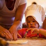 Het kleine jonge geitje met katten ziet kunst het koken met grootmoeder eigengemaakte cake in onder ogen de keuken Stock Afbeelding