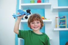 Het kleine jongen spelen met een stuk speelgoed vliegtuig Royalty-vrije Stock Foto