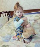 Het kleine Kaukasische spel van het kindmeisje met speelgoed op het bed Stock Afbeeldingen