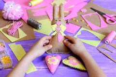 Het kleine kind houdt een gevoelde Paashaas met harten in zijn handen Kind gemaakt een leuk tot Pasen-muurdecor dat van gevoeld w Royalty-vrije Stock Afbeeldingen