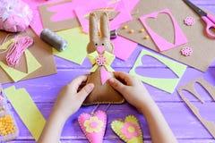 Het kleine kind houdt een gevoelde Paashaas in zijn handen Het kind maakte een gevoeld leuk konijntje met harten voor Pasen Royalty-vrije Stock Afbeeldingen