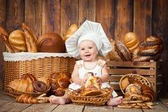 Het kleine kind kookt een croissant op de achtergrond van manden met broodjes en brood stock afbeelding