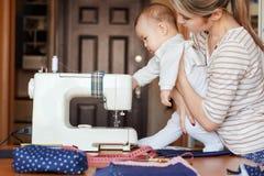 Het kleine kind leert nieuwe kennis, samen met zijn moeder inspecteert naaimachine Het werk thuis, ouderschap, ouders en royalty-vrije stock fotografie