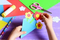 Het kleine kind maakt document ambachten voor moeder` s dag of verjaardag Klein kind die document bloemen voor mamma doen Eenvoud stock afbeelding