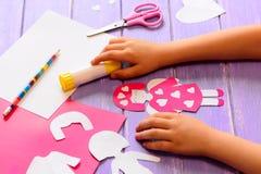 Het kleine kind maakte een engelenpop van karton De handen van kinderen op een houten lijst Royalty-vrije Stock Foto