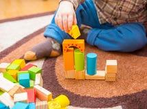 Het kleine kind spelen met houten blokken Stock Afbeelding