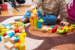 Het kleine kind spelen met houten blokken Royalty-vrije Stock Afbeeldingen