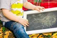 Het kleine kind trekt met krijt Stock Afbeelding