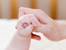 Het kleine kind wordt gehouden door de hand stock afbeeldingen