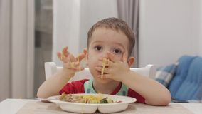 Het kleine kind zit bij een lijst in een slab en eet zijn eigen spaghetti, gewillig eet de leuke baby Leuk weinig baby stock footage