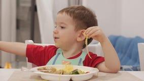 Het kleine kind zit bij een lijst in een slab en eet zijn eigen spaghetti, gewillig eet de leuke baby Leuk weinig baby stock videobeelden