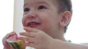 Het kleine kind zit bij een lijst in een slab en eet zijn eigen watermeloen, gewillig eet de leuke baby Leuk weinig baby stock video
