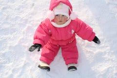 Het kleine kind zit op een sneeuw stock foto