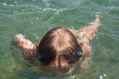 Het kleine kind zwemt onder op zee water, lerend te zwemmen Royalty-vrije Stock Afbeeldingen