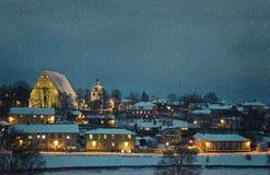 Het kleine landschap van de stadswinter in de avond met sneeuwval royalty-vrije stock afbeelding
