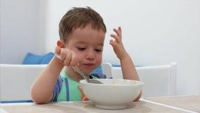 Het kleine leuke kind zit bij een lijst en eet zijn eigen havermeel, gewillig eet de baby Concepten gelukkige kinderjaren stock videobeelden