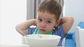 Het kleine leuke kind zit bij een lijst en eet zijn eigen havermeel, gewillig eet de baby Concepten gelukkige kinderjaren stock footage