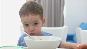 Het kleine leuke kind zit bij een lijst en eet zijn eigen havermeel, gewillig eet de baby Concepten gelukkige kinderjaren stock video