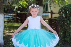 Het kleine leuke meisje in een blauwe en witte kleding en een kroon heft de boord van haar kleding op royalty-vrije stock afbeelding