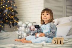 Het kleine leuke meisje is 2 jaar oude zittings dichtbij Kerstboom en het bekijken de kalender 31 van December Royalty-vrije Stock Foto's