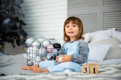 Het kleine leuke meisje is 2 jaar oude zittings dichtbij Kerstboom en het bekijken de kalender 31 van December Stock Afbeelding