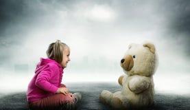 Het kleine leuke meisje zit en bekijkt stuk speelgoed draagt Stock Afbeeldingen