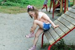 Het kleine meisje bekijkt haar kneuzing Royalty-vrije Stock Afbeelding