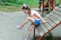 Het kleine meisje bekijkt haar kneuzing Royalty-vrije Stock Foto