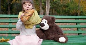 Het kleine meisje eet gevlecht broodje met papaver op bank met teddybeer bij speelplaats in de herfstpark stock footage