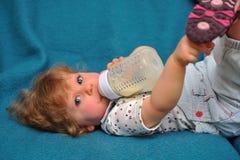 Het kleine meisje liggen op blauwe bank en drinkt melk van   Stock Foto's
