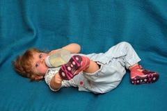 Het kleine meisje liggen op blauwe bank en drinkt melk van fles Royalty-vrije Stock Afbeeldingen
