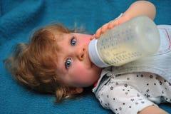 Het kleine meisje liggen op blauwe bank en drinkt melk van fles Stock Afbeelding