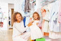 Het kleine meisje met haar moeder kiest de juiste kleding Royalty-vrije Stock Fotografie