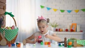 Het kleine meisje praktizeren in eieren die, stewardess die voor Pasen, tradities voorbereidingen treffen kleuren stock footage