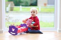 Het kleine meisje spelen met haar pop Stock Foto