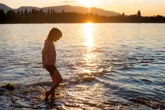 Het kleine meisje spelen in rivierwater bij zonsondergang Royalty-vrije Stock Fotografie