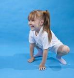 Het kleine meisje stelt als kikker op blauw Stock Afbeeldingen
