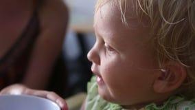 het kleine meisje van de blondebaby eet stock video