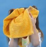 Het kleine meisje veegt zijn geïsoleerdk gezicht af door handdoek Stock Foto's