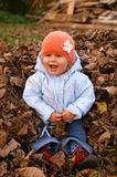 Het kleine meisje zit op bladeren royalty-vrije stock afbeeldingen
