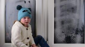 Het kleine meisje zit op vensterbank achter het bevroren venster stock footage