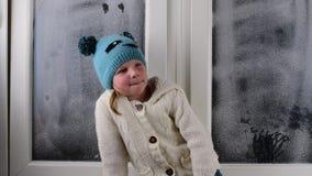 Het kleine meisje zit op vensterbank achter het bevroren venster stock video