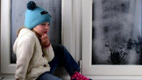 Het kleine meisje zit op vensterbank achter het bevroren venster Lage DOF stock video
