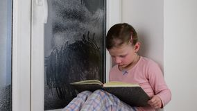 Het kleine meisje zit op vensterbank achter het bevroren venster Het leuke meisje zit op vensterrichel en leest het boek stock video