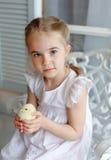Het kleine roodharige meisje die met vlechten een geel kuiken houden, stock fotografie